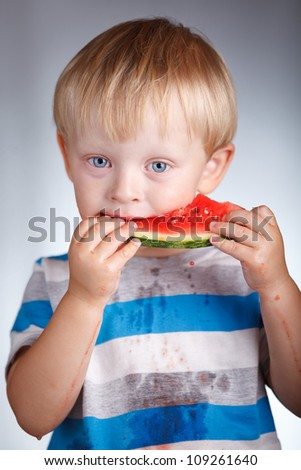 portrait of a handsome kid holding a watermelon and tasting it over a grey background
