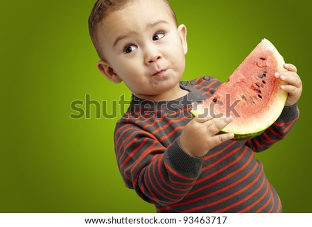 portrait of a handsome kid holding a watermelon and tasting over green background