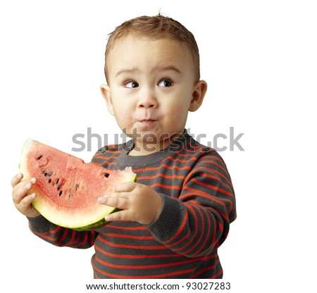 portrait of a handsome kid holding a watermelon and tasting over white