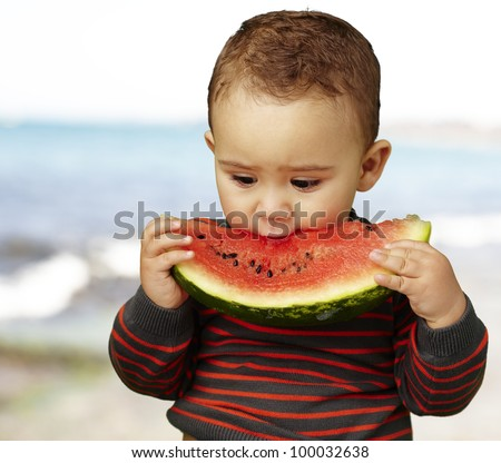portrait of a handsome kid holding a watermelon piece and tasting it at the shore