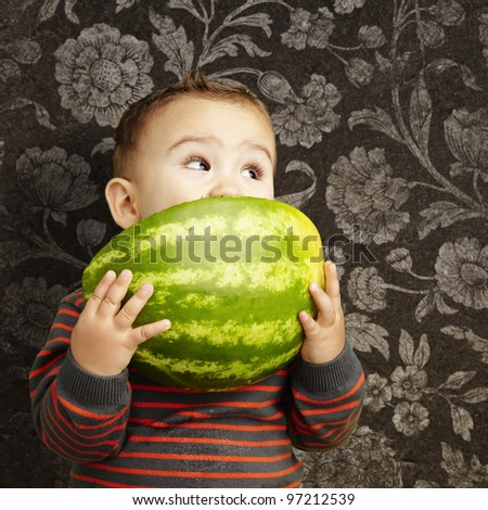 portrait of a handsome kid holding watermelon and sucking against a vintage background - stock photo