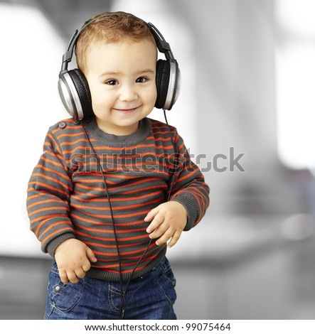 portrait of a handsome kid listening to music and smiling indoor