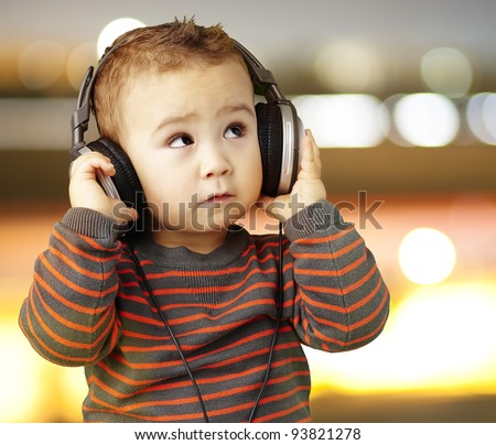 portrait of a handsome kid listening to music looking up against a city background