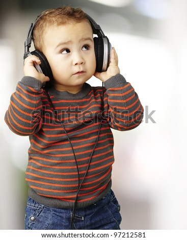 portrait of a handsome kid listening to music looking up indoor