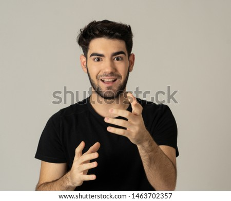 Portrait of a handsome latin young man surprised and shocked hearing great news. Attractive male looking amazed with wide eyes and mouth open in surprise. Human facial expressions and emotions. #1463702357
