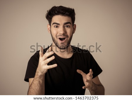 Portrait of a handsome latin young man surprised and shocked hearing great news. Attractive male looking amazed with wide eyes and mouth open in surprise. Human facial expressions and emotions. #1463702375