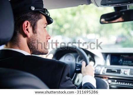Portrait of a handsome male chauffeur riding car Foto stock ©