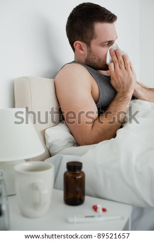 Portrait of a handsome man blowing his nose in his bedroom