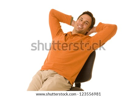 portrait of a handsome man casual dressed wearing khakis and an orange sweater leaning back on an office chair isolated on a white background