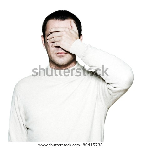 Portrait of a handsome man covering his eyes with hand in studio on white isolated background