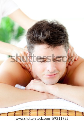 Portrait of a handsome man having a back massage in a spa center