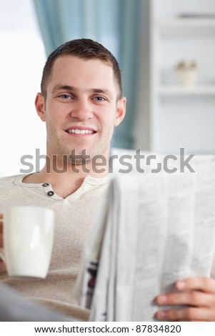 Portrait of a handsome man having a coffee while reading the news in his living room