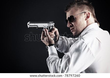 Portrait of a handsome man holding a gun. Studio shot.