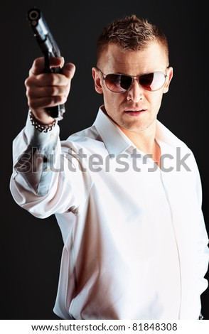Portrait of a handsome man holding a gun. Studio shot.