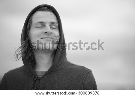 Portrait of a handsome man in a hoodie breathing some fresh air