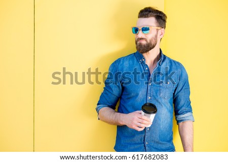Portrait of a handsome man in blue t-shirt standing with coffee to go on the yellow background #617682083