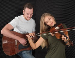 Portrait of a handsome man musician plays the guitar, a beautiful woman musician plays the violin in the recording studio.