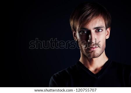 Portrait of a handsome man over black background.