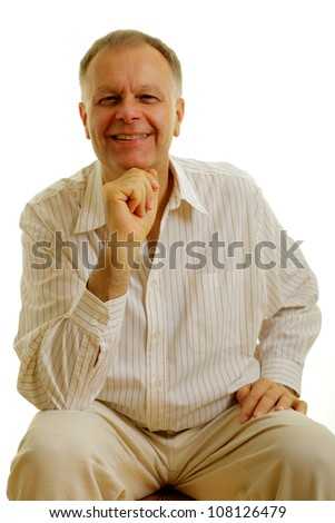 Portrait of a handsome man sitting with hand under his chin on a white background.