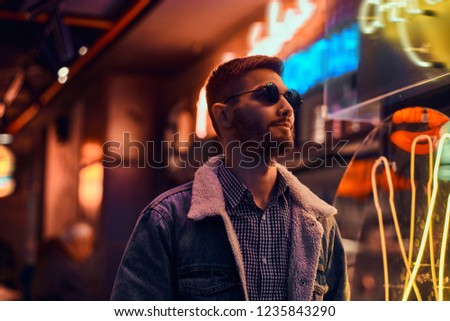Portrait of a handsome man standing in the night on the street. Illuminated signboards, neon, lights. #1235843290