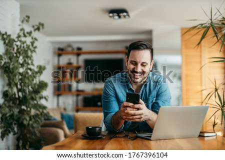 Portrait of a handsome man text messaging over smart phone, at home.