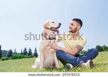 Portrait of a handsome man wearing yellow t-short and jeans with tattoo on his arm sitting on the grass, looking smiling on his lovely golden retriever in the park