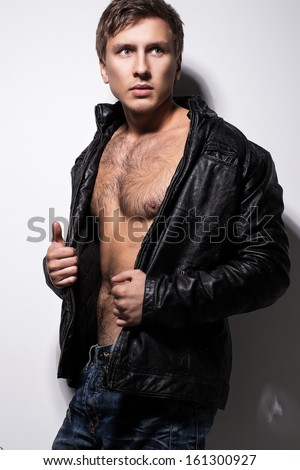 Portrait of a handsome man who covers his naked body with leather jacket over a light background
