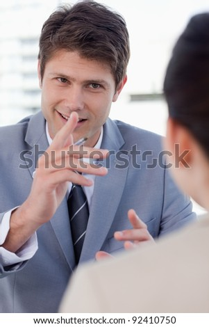 Portrait of a handsome manager interviewing a female applicant in his office