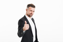 Portrait of a handsome mature businessman dressed in suit showing thumbs up gesture isolated over white background
