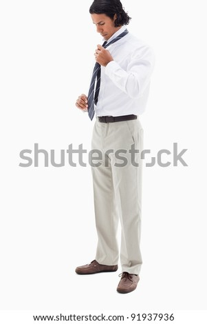 Portrait of a handsome office worker putting his tie against a white background - stock photo