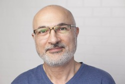 Portrait of a handsome positive 50 years old man with glasses, unshaven hair in a blue t-shirt indoors.