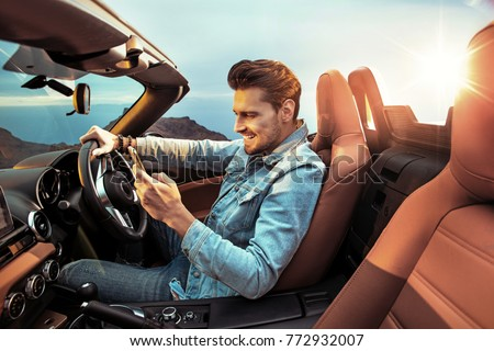 Portrait of a handsome, rich guy driving his convertible car #772932007