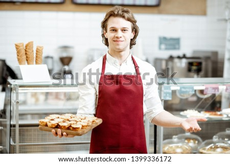 Portrait of a handsome salesman or confectioner in red apron standing with fresh baked pastel de nata in the pastry shop Stockfoto ©