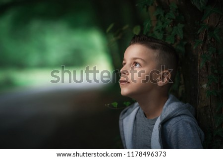 portrait of a handsome seven year old boy.young and strong character, a young boy looking up