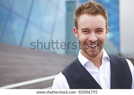 Portrait of a handsome smiling young business man. Outdoor photo.