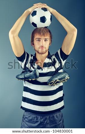 Portrait of a handsome soccer player. Studio shot.