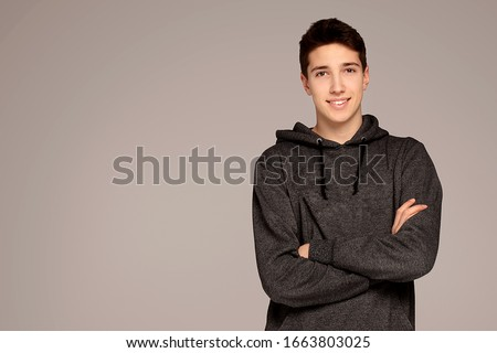 Portrait of a handsome teenage boy in hoodie posing over gray background. Studio shot. Teen fashion.
