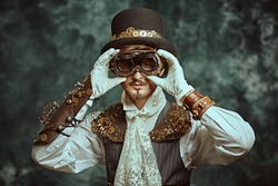 Portrait of a handsome victorian steampunk man on a grunge background. Fantasy world, scientific inventions. Copy space.