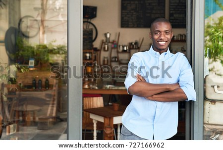 Portrait of a handsome young African entrepreneur smiling and standing with his arms crossed at the entrance of his trendy cafe