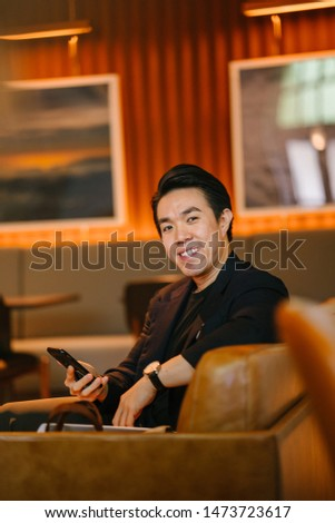 Portrait of a handsome, young and fit man in a stylish casual outfit smiling as he lounges on a leather couch in a warmly lit room on his own.  #1473723617