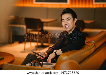 Portrait of a handsome, young and fit man in a stylish casual outfit smiling as he lounges on a leather couch in a warmly lit room on his own.  #1473723620