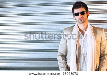 Portrait of a handsome young business man leaning against the wall.