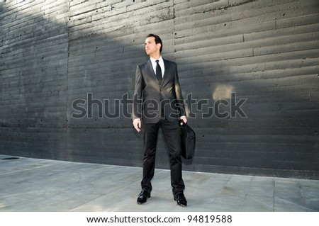 Portrait of a handsome young business man standing in the street with a briefcase
