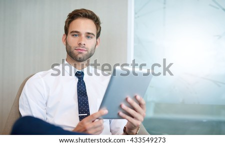 purchase portrait of a handsome young businessman sitting in a bright modern office space holding a digital bright modern office space