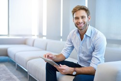Portrait of a handsome young businessman sitting on a modern couch, holding a digital tablet, and smiling broadly at the camera