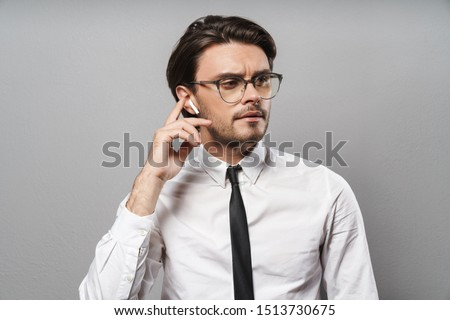 Portrait of a handsome young businessman wearing suit standing isolated over gray background, listening to music with wireless earphones