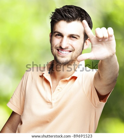 portrait of a handsome young man gesturing against a nature background
