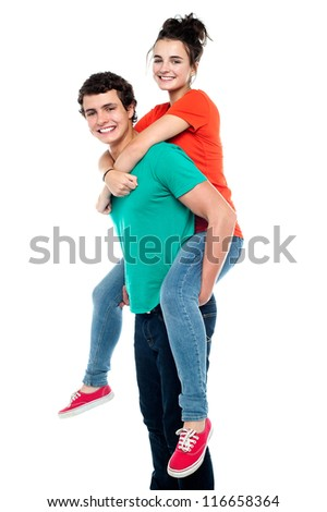 Portrait of a handsome young man giving a piggyback ride to his girlfriend - Indoor