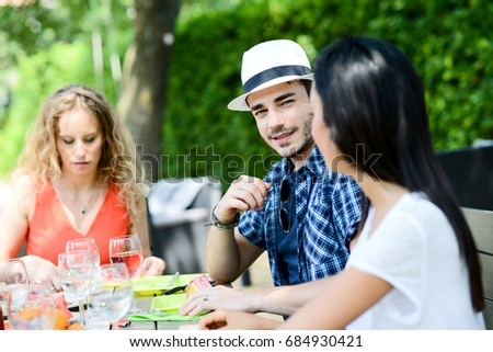 portrait of a handsome young man having lunch party with group of friends outdoor in summer