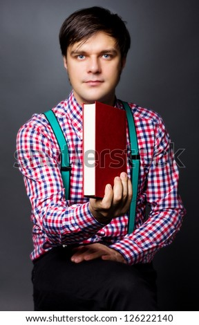 Portrait of a handsome young man holding a book  on gray background